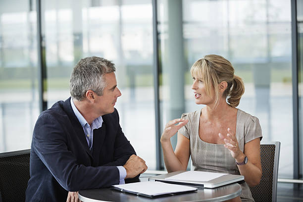 Two business people sitting, having a conversation Businessman and woman having discussion at table in office. face to face stock pictures, royalty-free photos & images