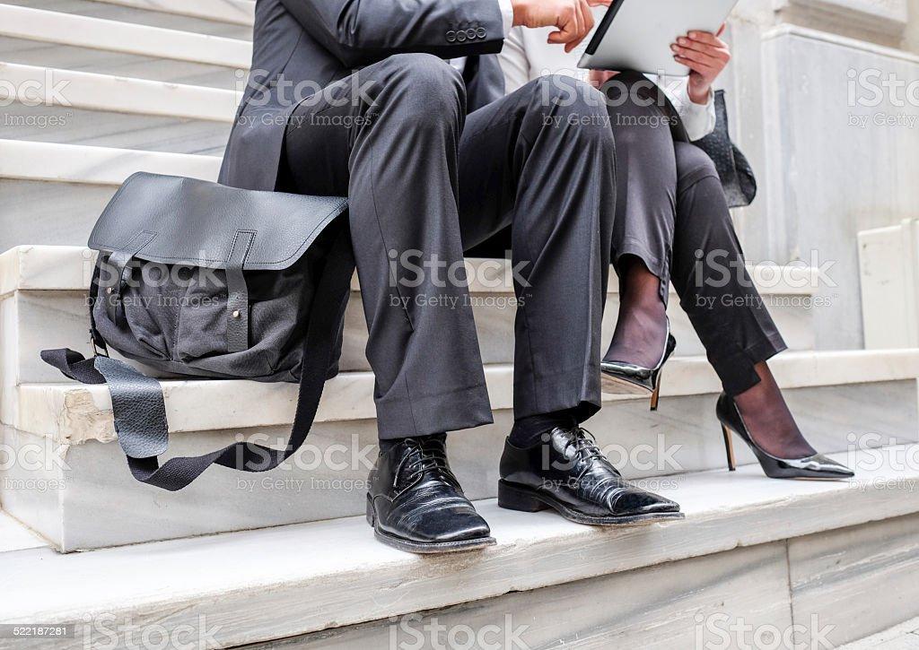 two business people sitting on steps. stok fotoğrafı