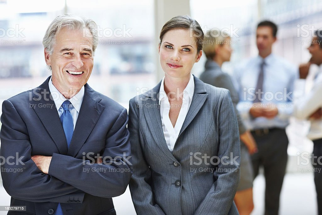 Two business people standing while their team in blur background royalty-free stock photo
