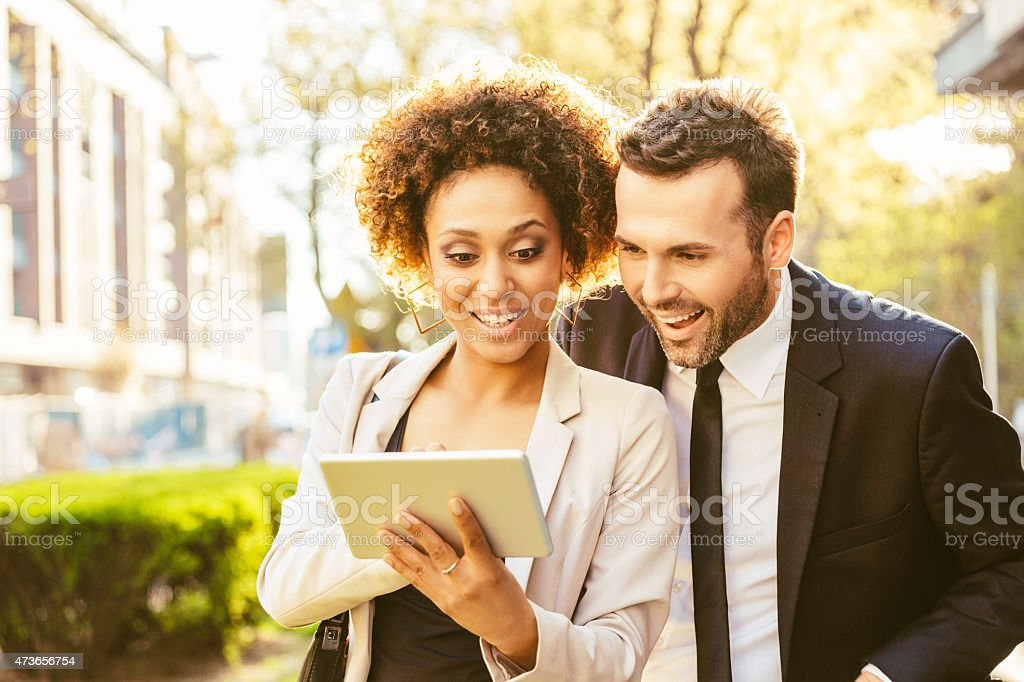 Two business people using digital tablet outdoor at sunset Portrait of cheerful caucasian businessman and afro american businesswoman in formal outfits using a digital tablet together outdoor at sunset.  2015 Stock Photo
