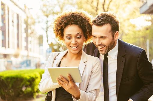 Two Business People Using Digital Tablet Outdoor At Sunset Stock Photo - Download Image Now