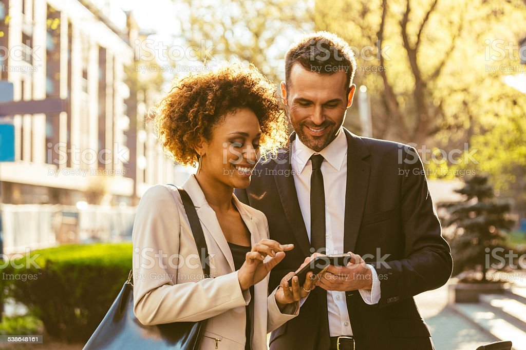 Two business people using smart phones outdoor stock photo