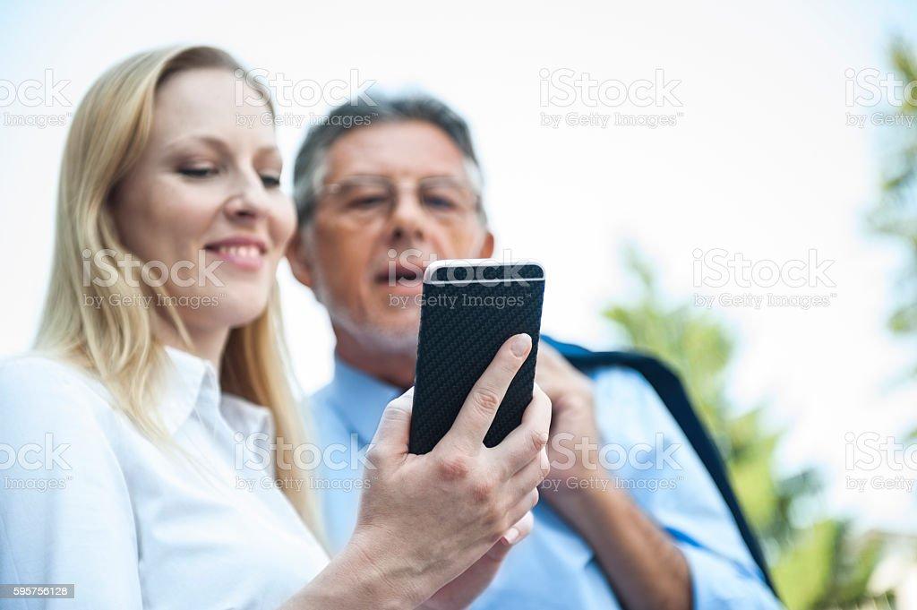 Smiling business people taking selfie, using smart phone
