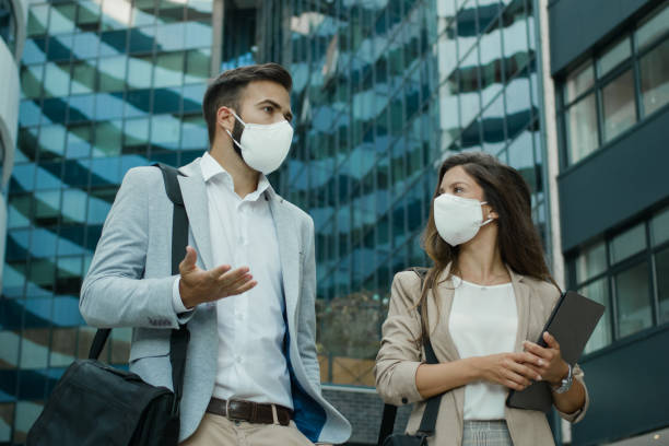 Two business people wearing protective face masks and talking to each outdoors stock photo