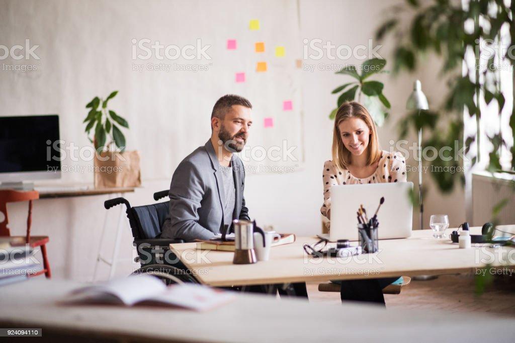 Zwei Geschäftsleute mit Rollstuhl im Büro. – Foto