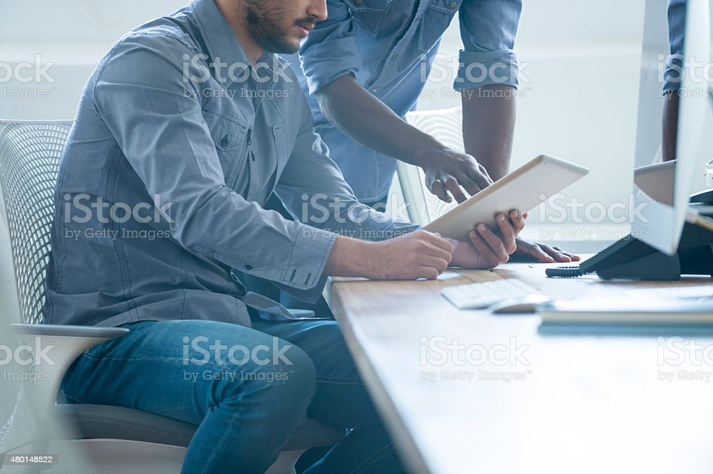 Two business people working on a digital tablet. stock photo