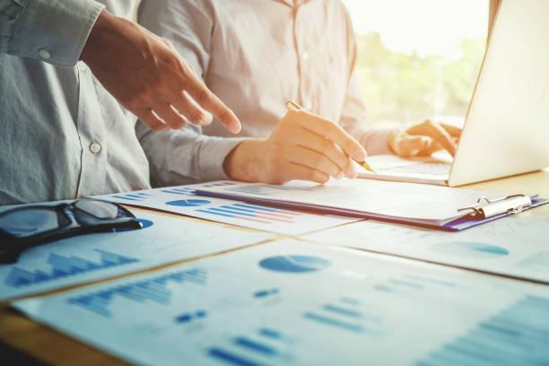 2 ビジネス人技術とラップトップの会議に一緒に取り組んで - 柱頭 ストックフォトと画像