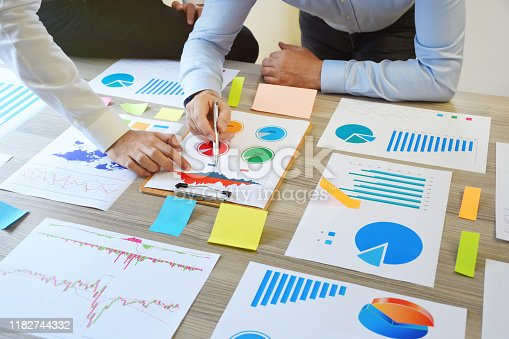 1068752548 istock photo Two business person working on the office desk with business graphs 1182744332