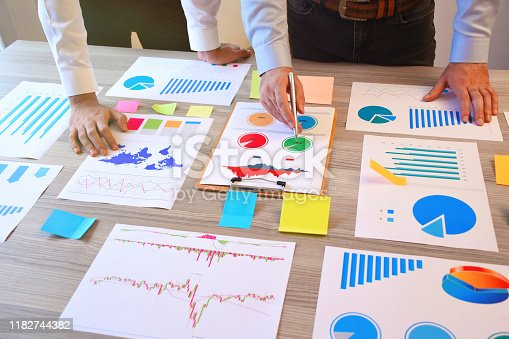 1068752548 istock photo Two business person working on the office desk with business graphs 1182744382