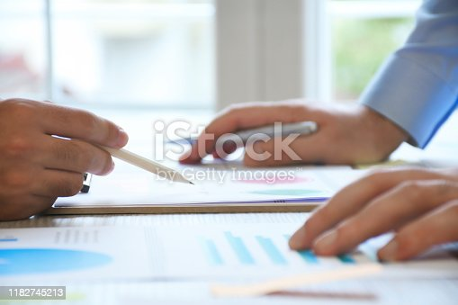 1068752548 istock photo Two business person working on the office desk with business graphs 1182745213