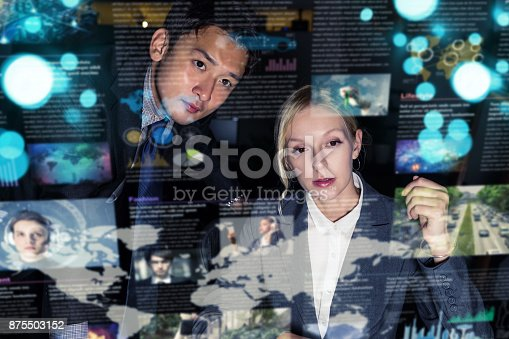 875503222 istock photo Two business persons in front of futuristic display. Graphical User Interface(GUI). Head up Display(HUD). Internet of things. 875503152