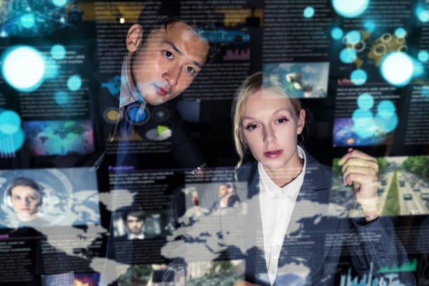 Two business persons in front of futuristic display. Graphical User Interface(GUI). Head up Display(HUD). Internet of things. stock photo