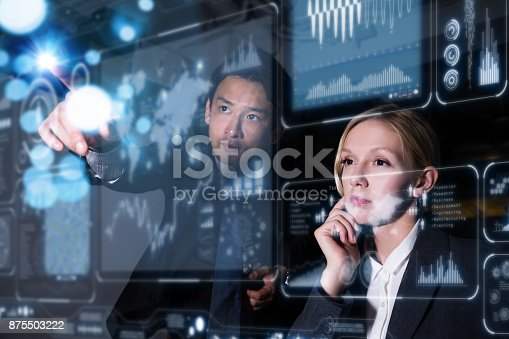 istock Two business persons in front of futuristic display. Graphical User Interface(GUI). Head up Display(HUD). Internet of things. 875503222