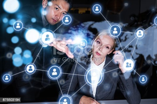 693586040istockphoto Two business persons in front of futuristic display. Social networking concept. 875503194