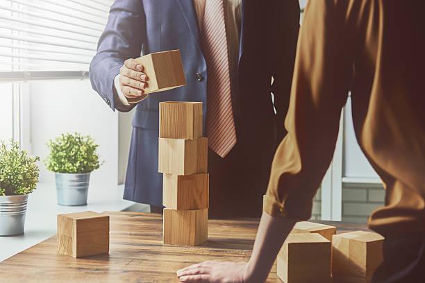 two business persons - hand constructing industry stockfoto's en -beelden