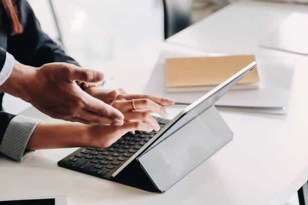 Zwei Geschäftsteams diskutieren neue Plan-Finanzdiagrammdaten auf dem Bürotisch mit digitalem Tablet. – Foto