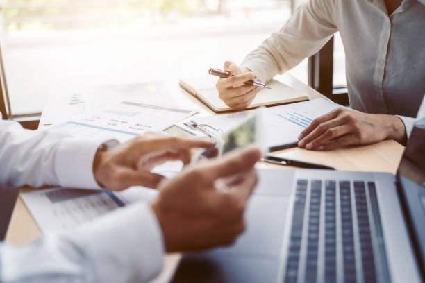Two business teamwork calculating a valuation in workplace. stock photo