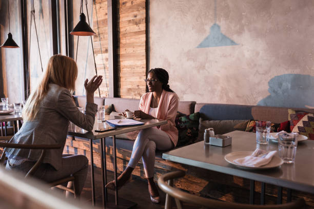 Two business women having coffee break in high-end restaurant Two business women at the cafe restaurant discussing during coffee break coffee shop stock pictures, royalty-free photos & images