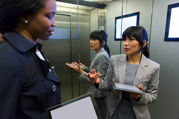 Two business women in elevator discussing,using digital tablets – Foto