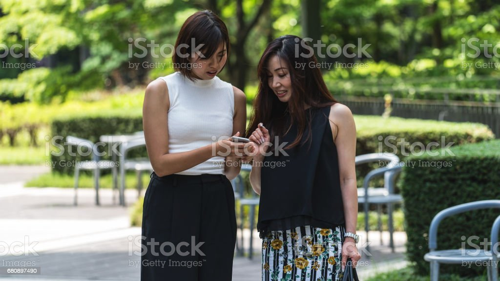 Two business women watching smartphone outside royalty-free stock photo