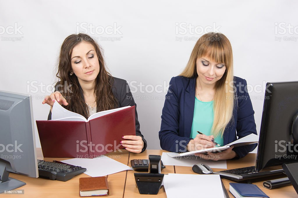 Two business women working in the office with one desk stock photo