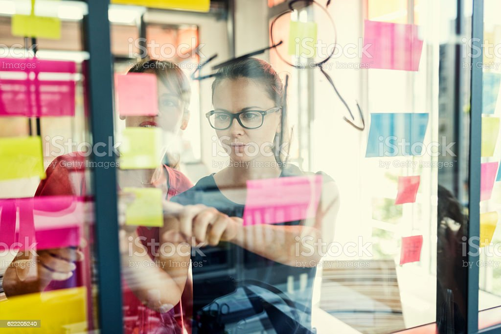 Two business women working together on wall glass