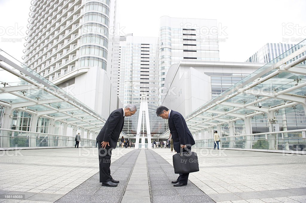 Two businessman bowing to each other on a pedestrian bridge stock photo