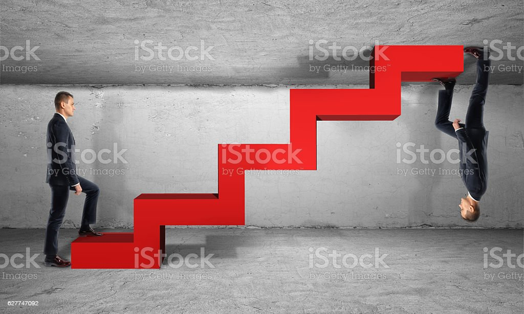 Two businessman climb one red ladder from different sides stock photo