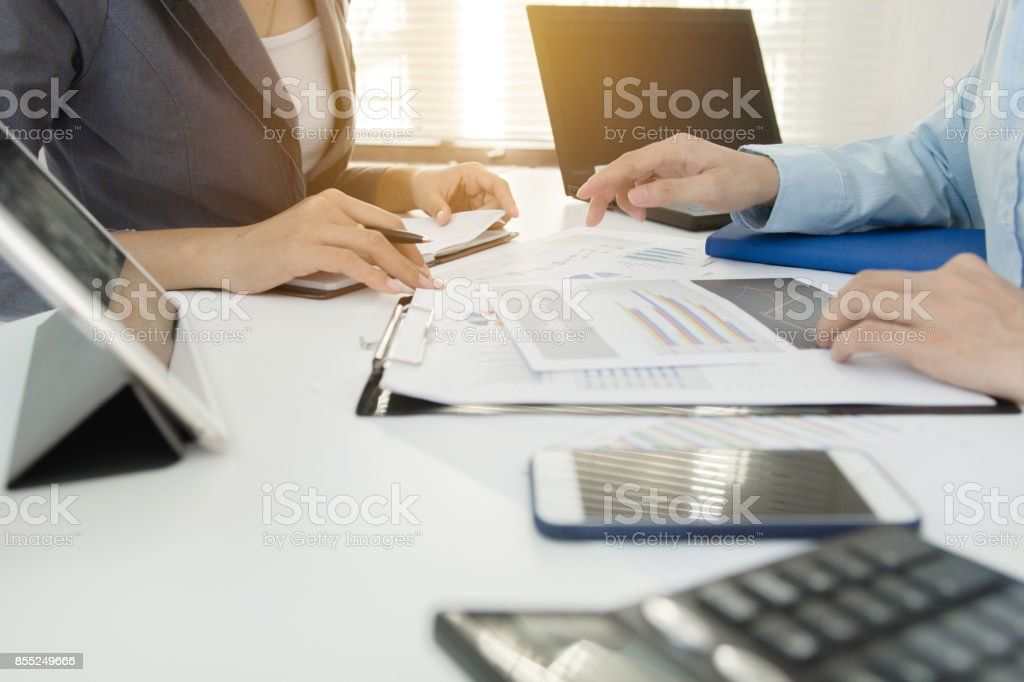 Two businessman colleagues discussing plan with financial graph data on office table with laptop, Concept co working, Business meeting stock photo