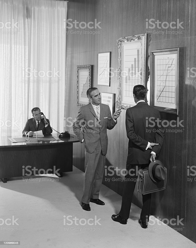 Two businessman discussing at bar chart while another man using telephone in background stock photo