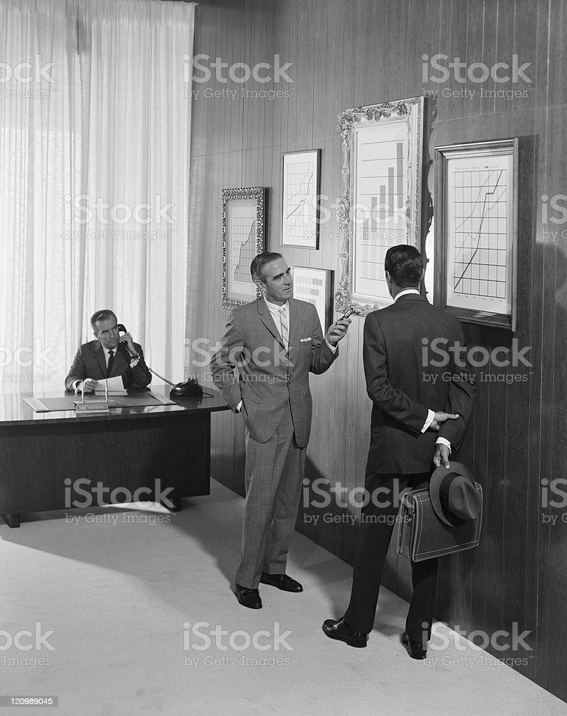 Zwei Geschäftsmann über an der bar, während ein Mann mit chart – Foto