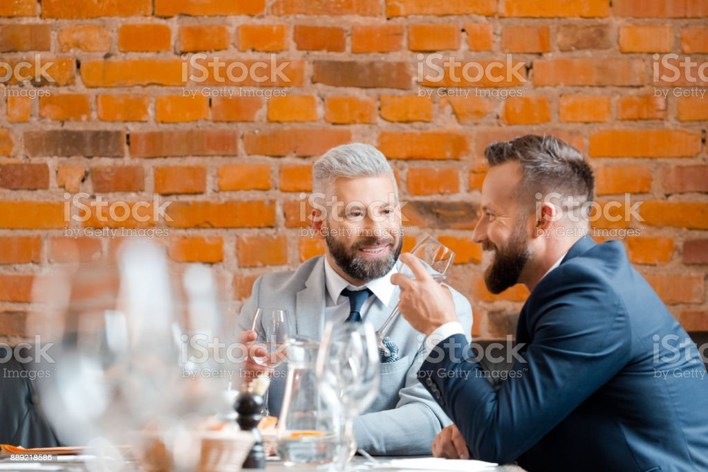 Two businessman having a successful meeting at restaurant Two businessman sitting a restaurant table and smiling. Business partners having a successful meeting at restaurant. 30-39 Years Stock Photo