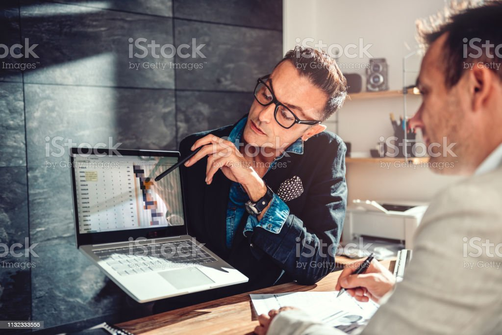 Two businessman reviewing project timeline on a meeting stock photo