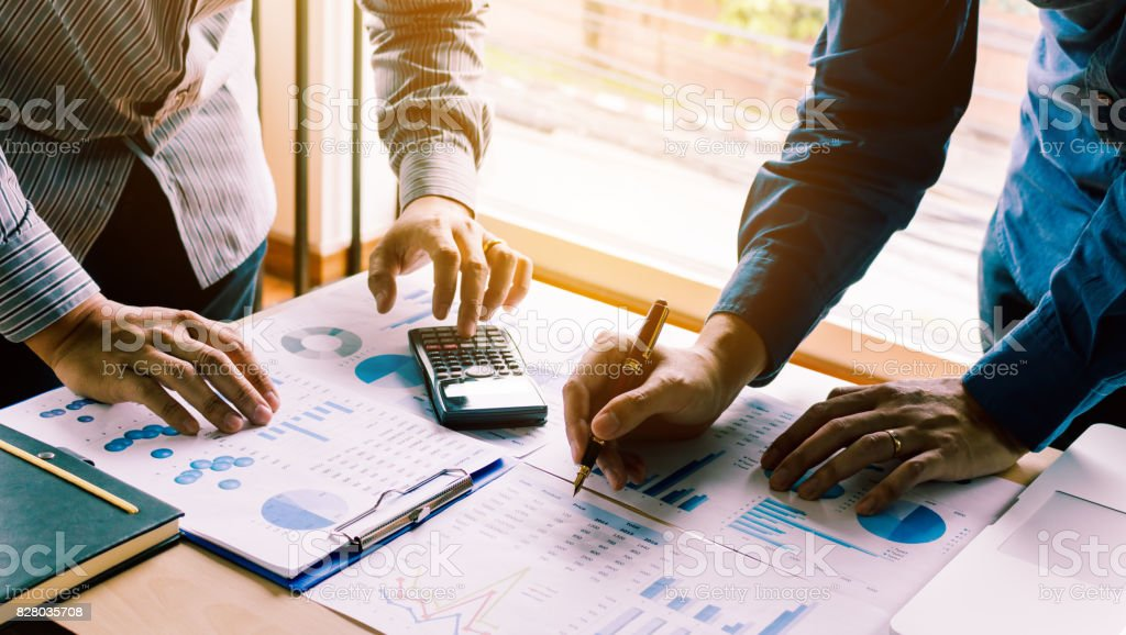 Two businessman team calculate about summary report annual on table office. stock photo