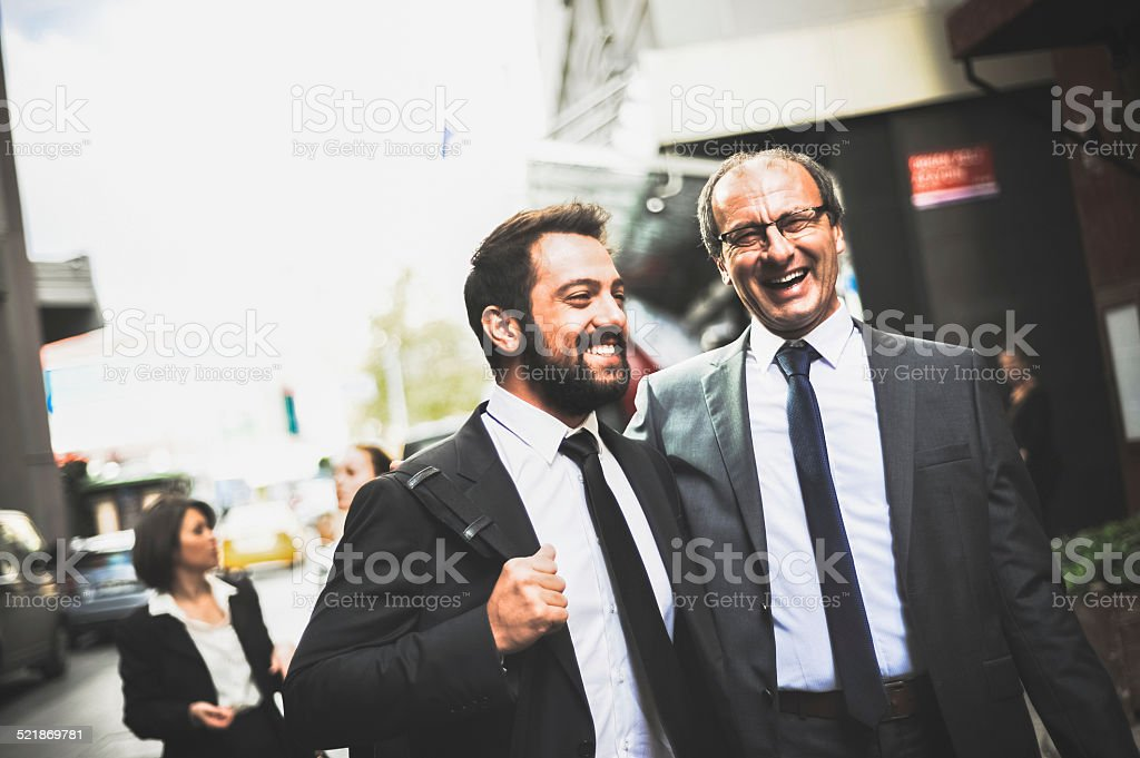 Two businessman walking on a street stock photo