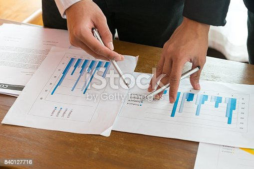 istock Two Businessmans disccussing with finance graph chart 840127716