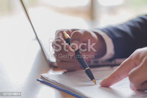 istock Two businessmen analyzing stats financial data on pc laptop, pointing at screen with rising graph and charts, discussing company growth, 1072076824