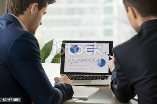 istock Two businessmen analyzing stats on laptop, accounting software, rear view 804671552