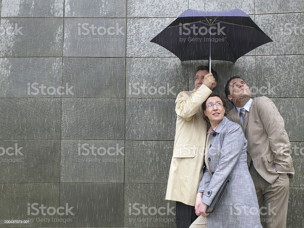 Two businessmen and woman sharing umbrella in rain royalty-free stock photo