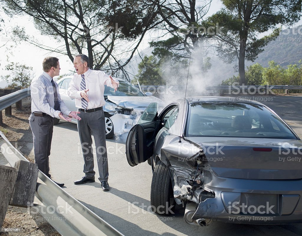 Two businessmen arguing about damaged cars royalty-free stock photo