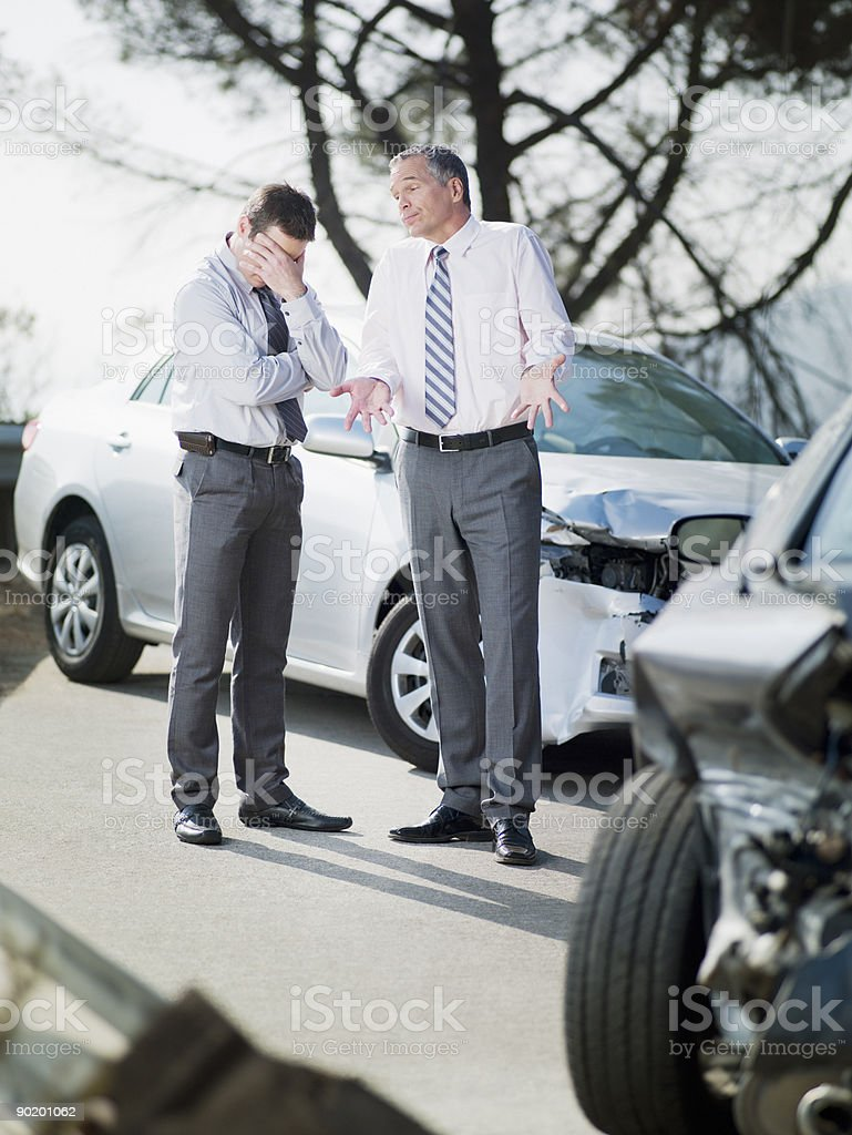 Two businessmen arguing about damaged cars stock photo