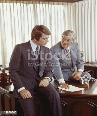 istock Two businessmen at desk looking at document 119679202