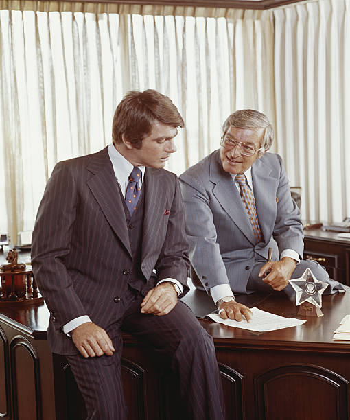 Two businessmen at desk looking at document stock photo