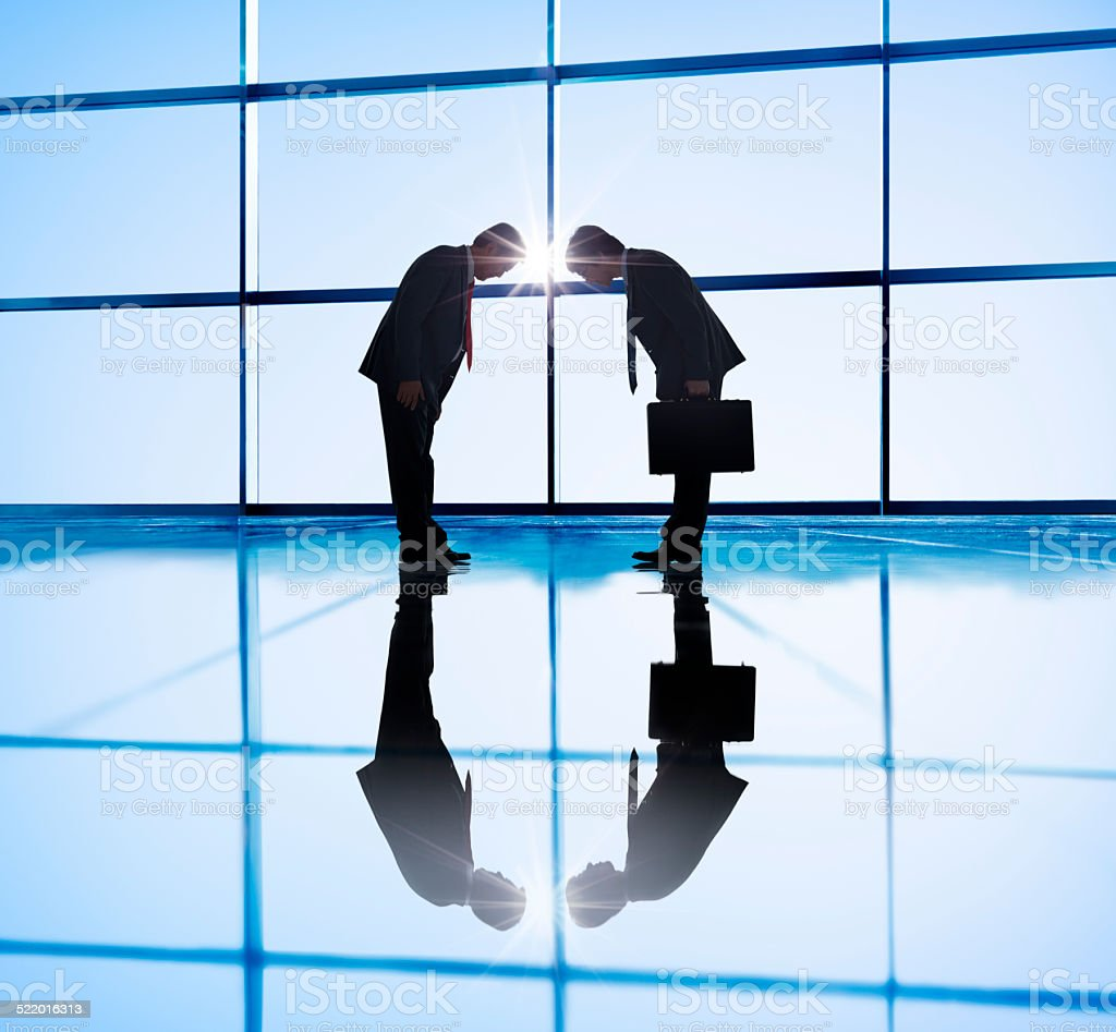 Two Businessmen Bowing in Back Lit stock photo