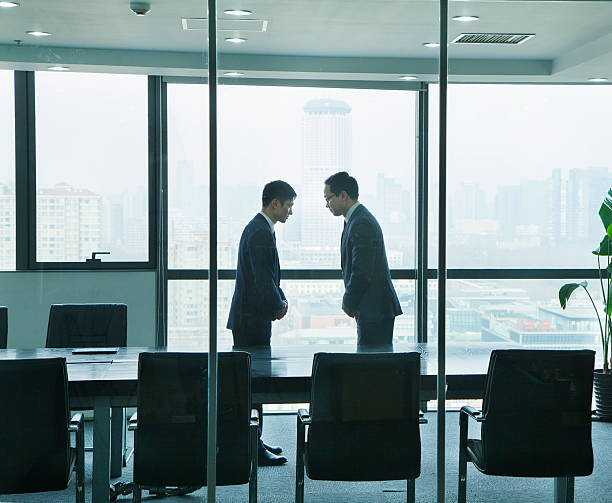 Two Businessmen Bowing to Each Other stock photo