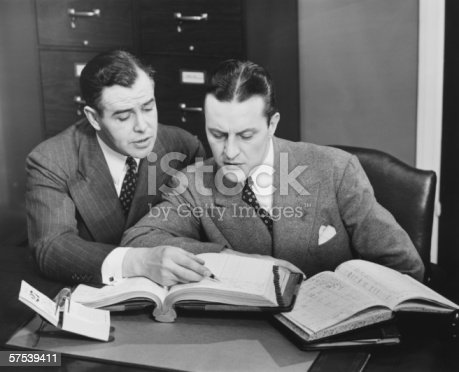 istock Two businessmen checking trading books, (B&W) 57539411