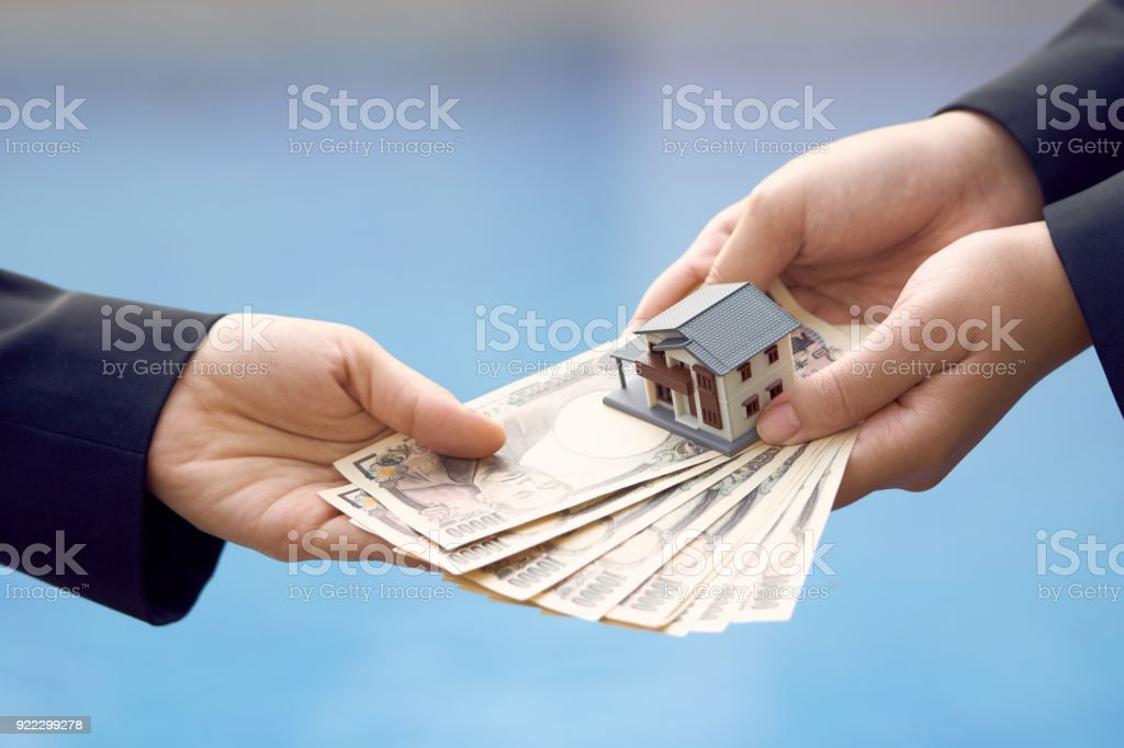 Two businessmen conduct a house sale with a model house and Yen banknotes valued at 10000 yen.using as background business concept and real estate concept with copy space for your text or design. stock photo