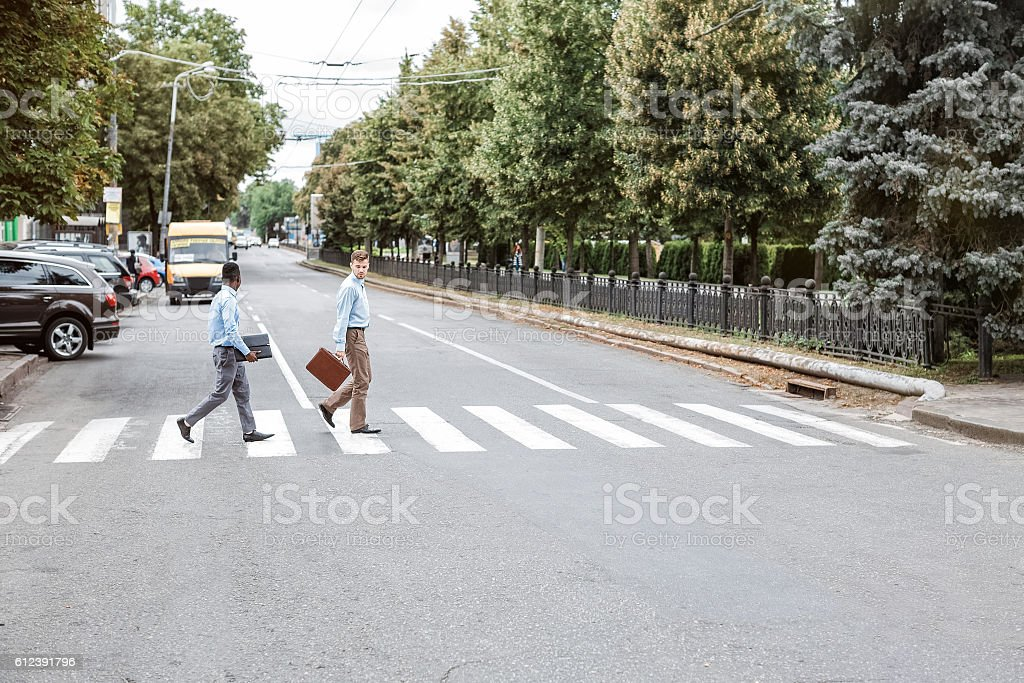 two businessmen  crossing the road stock photo