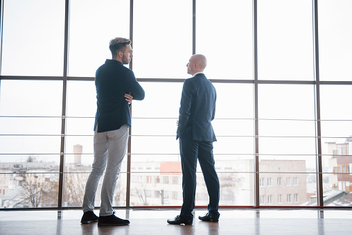 Two Businessmen Deep In Discussion Together While Standing