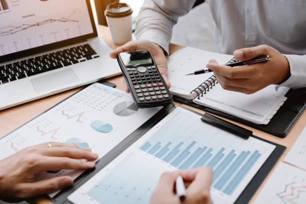 dos hombres de negocios discuten el análisis compartiendo cálculos sobre el presupuesto de la empresa y la planificación financiera juntos en el escritorio en la sala de oficinas. - financial planning fotografías e imágenes de stock